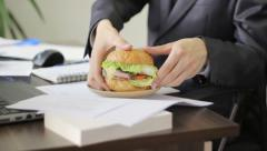 Lunch break in job, man eating hamburger, fast food, dolly shot Stock Footage
