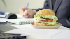 Man eating unhealthy food at job, lunch break, fast food, static - stock footage