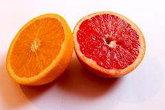 Orange and grapefruit divided in half Stock Photos