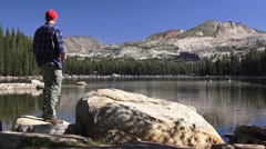 Fisherman on mountain lake, reflection Stock Footage