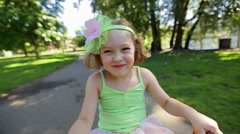Cute 5 Year Old Girl With A Big Smile Rides Her Tricycle In The Park Stock Footage