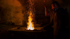 Blacksmith heats the metal to the flame Stock Footage