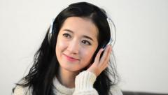 Horizontal shot of Asian woman teenager listing love music with big Headphone Stock Footage