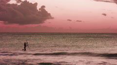4K Paddle boarder in the ocean at sunset Stock Footage