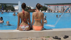 Amazing beautiful young girls in bathing suits sitting and swimming in the pool Stock Footage