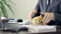 Man eating big delicious hamburger in the office, a short lunch break, fast food Stock Footage