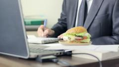 Worker eating a big hamburger during his lunch break at the office, fast food Stock Footage
