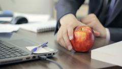 Man eating a big apple during his lunch break in the office, healthy food - stock footage
