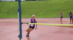 Teenage Blonde Girl Clears High Jump Bar Stock Footage