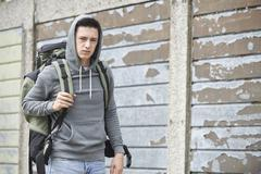 Homeless teenage boy on street with rucksack Stock Photos