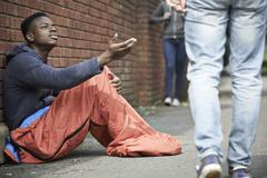 homeless teenage boy begging for money on the street - stock photo