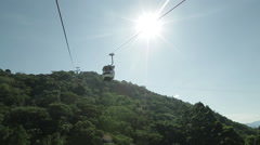 Cable car moving on a sunny day with mountains in Balneario Camboriu. zoom in Stock Footage