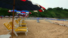 Sun umbrellas and chaise longues on Naiharn beach, Phuket, Thailand Stock Footage