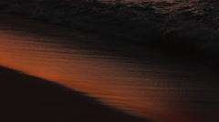 Waves gliding onto the beach at sunset in 4K Stock Footage