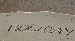 Holiday sign in sand on beach Stock Footage