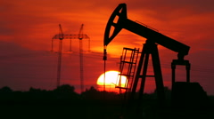 Oil Field Pump with Power line Tower in Sunset Stock Footage