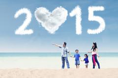 Family walking at beach under cloud of 2015 Stock Illustration