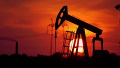Oil pump in the field with sunset in the back - stock footage