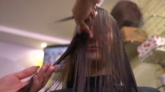 Hair stylist makes hairstyle to young girl Stock Footage
