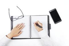 Hands write a list on personal agenda Stock Photos