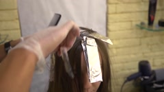 Hair stylist makes hairstyle to young girl applying paint to the hair Stock Footage