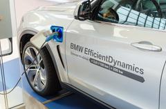 New model of bmw x5 with hybrid engine at charging station Stock Photos