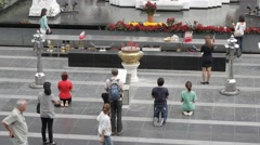 Buddhists pass by and pray to monument, Bangkok Stock Footage