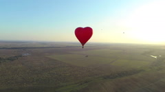 Hot air balloon in the shape of heart flies away. Aerial view - stock footage