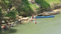 Children Bathing and Swimming at River's Edge Stock Footage