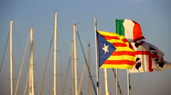 Italian,Sardinian and Catalan flags waving in the sunrise at Alghero harbor. Stock Footage