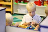 Stock Photo of young preschool children playing building blocks in school classroom