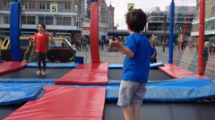 Two kids jump on a trampolin Stock Footage