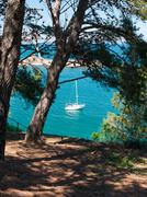 sailboat anchored in a bay - stock photo
