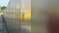 Street - sidewalk with people - wall (fence) from metal Stock Footage