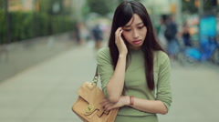 Young Asian woman walking worried depressed sad in city - stock footage
