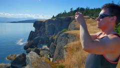 4K Sporty Man Taking Photos on Rock Bluff Overlooking Ocean Stock Footage