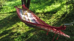 Striped hammock dangles in the wind Stock Footage