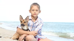 girl sitting on the coast hugging her dog - stock footage