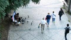 Homeless man feeds pigeons on the street - people walk around him - pavement Stock Footage
