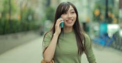 Young Asian Woman walking street talking on cellphone 4k - stock footage