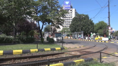 Streetcar railway, rails take a curve, green area downtown, people wait for tram Stock Footage