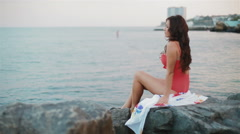 Beautiful, young, attractive European woman in a swimsuit on the stone beach Stock Footage