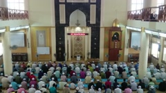 Crowds of muslim men listening to khutbah or preaching by the imam for prayer - stock footage