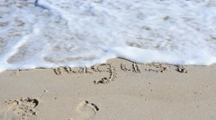 The inscription on the sand in August, a wave washed off Stock Footage