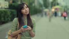 Young Asian Woman texting cellphone in city - stock footage