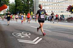 Senior woman runs in atlanta peachtree road race Stock Photos