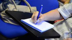 Writing in a notebook in a lecture or presentation Stock Footage