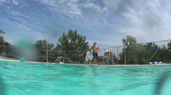 Slow motion of man trying to catch football as he jumps in pool Stock Footage