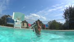 Man in pool squirting camera with toy Stock Footage