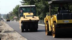 Stock Video Footage of Roadwork. Paving. Road rollers flattens asphalt. Steamrollers smoothing asphalt.